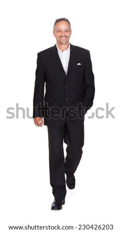 Full length portrait of smiling mature businessman walking over white background - stock photo