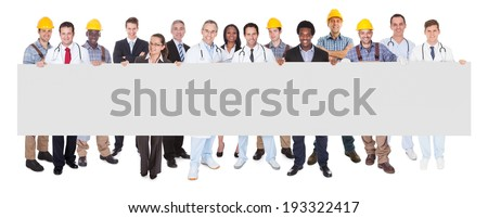 Full length portrait of smiling people with various occupations holding blank billboard over white background - stock photo