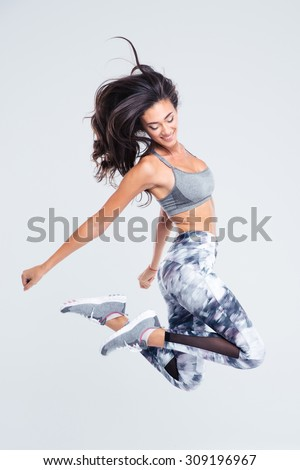 Full length portrait of smiling sports woman jumping isolated on a white background - stock photo