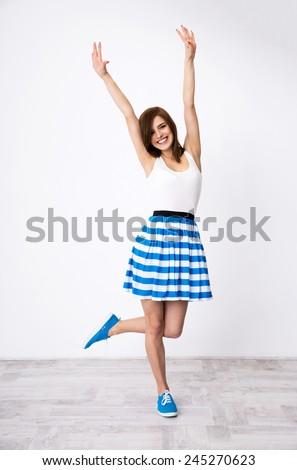 Full length portrait of smiling woman with raised hands up - stock photo