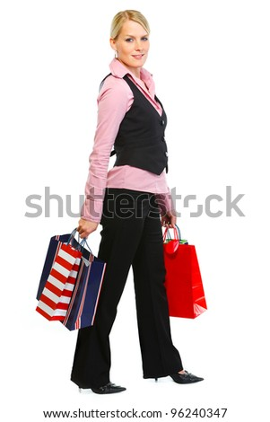 Full length portrait of smiling woman with shopping bags - stock photo