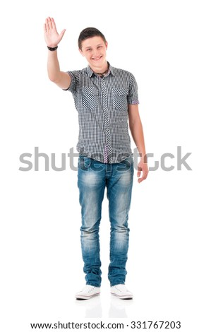 Full length portrait of smiling young man greets with his hand, isolated on white background - stock photo