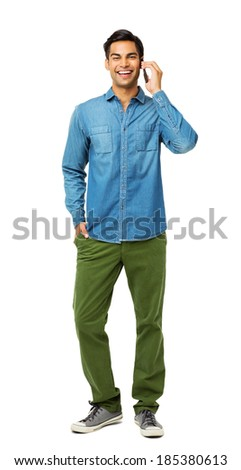 Full length portrait of smiling young man with hand in pocket answering smart phone over white background. Vertical shot. - stock photo