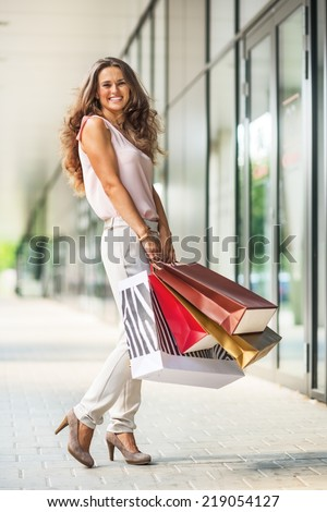 Full length portrait of smiling young woman with shopping bags on the mall alley - stock photo