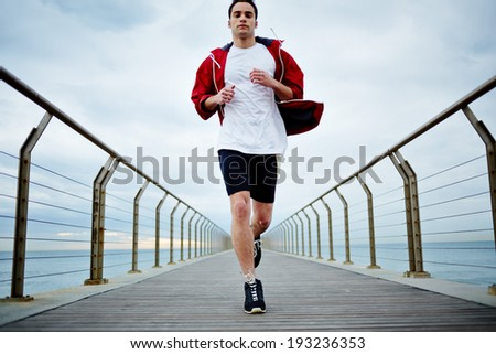 Full length portrait of sporty guy running fast along beautiful pier - stock photo