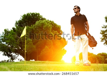 Full length portrait of stylish golfer in glasses standing on golf course with amazing flare sunset light on background, handsome man with golf bag on shoulder standing on golf course, filtered image - stock photo