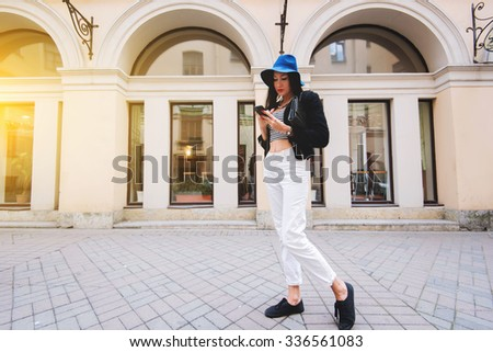 Full length portrait of stylish hipster girl chatting on her mobile phone while standing on the street in autumn day, young woman dressed in trendy clothes using cell telephone during walking in city - stock photo
