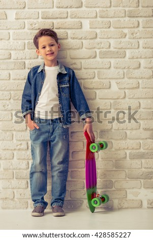 Full length portrait of stylish little boy in jeans clothes looking at camera and smiling, standing with skateboard against white brick wall - stock photo