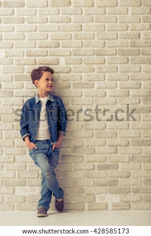 Full length portrait of stylish little boy in jeans clothes looking away and smiling, standing with hands in pockets against white brick wall - stock photo