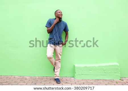 Full length portrait of stylish young african man standing against a green wall and looking away - stock photo