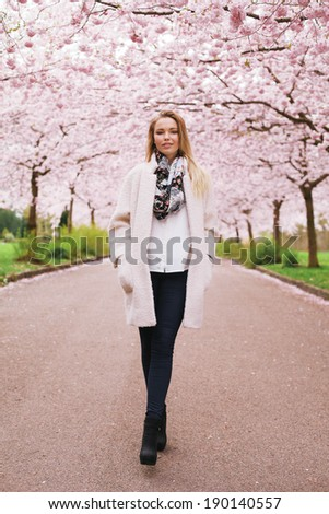 Full length portrait of stylish young woman walking at spring park. Fashionable female model at spring blossom park - Outdoors - stock photo