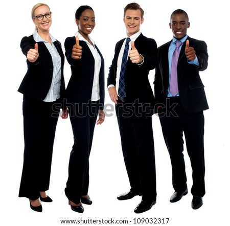 Full length portrait of successful corporate team gesturing thumbs up - stock photo