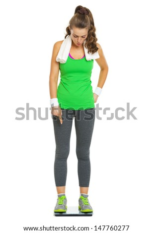 Full length portrait of surprised fitness young woman standing on scales - stock photo