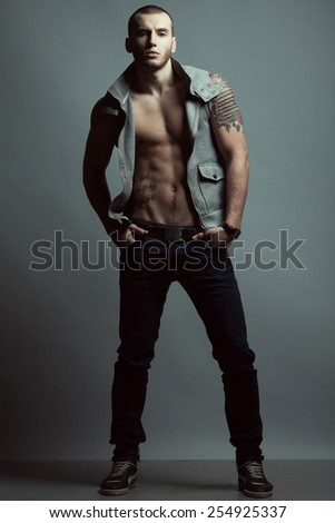 Full length portrait of tattooed brutal young man with short hair, bristle on face wearing sleeveless jacket, blue jeans, sneakers, posing over gray background. Hipster style. Studio shot - stock photo