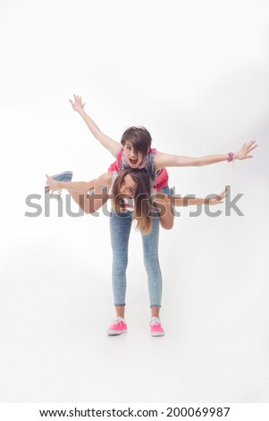 Full length portrait of teenage girls having fun raising their hands as flying. Isolated on white background. Concept of love, freedom, youth, friendship - stock photo