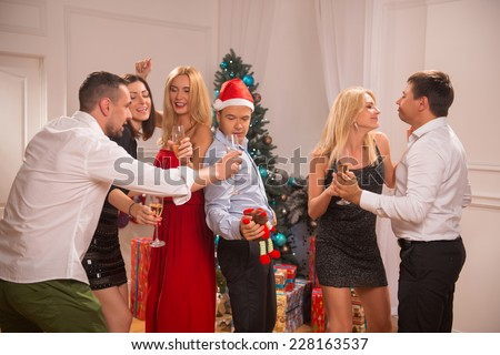 Full-length portrait of the company of happy friends wearing great costumes dancing near the Christmas tree celebrating New Year drinking champagne - stock photo