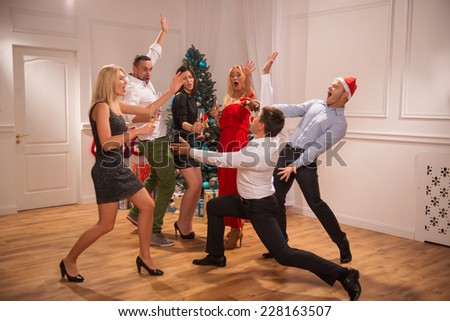 Full-length portrait of the company of happy friends wearing great costumes dancing together near the Christmas tree celebrating New Year drinking champagne one of them standing on his knees back to - stock photo
