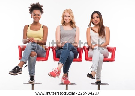 Full-length portrait of three young lovely smiling girls wearing colorful T-shirts and jeans sitting on the red wonderful chairs. Isolated on white background - stock photo