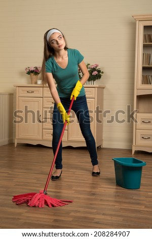 Full-length portrait of tired dark-haired housemaid wearing yellow rubber gloves scrubbing floor and dreaming about the rest - stock photo