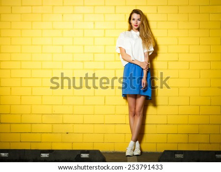 Full Length Portrait of Trendy Hipster Girl Standing at the Yellow Brick Wall Background. Urban Fashion Concept. Copy Space. - stock photo