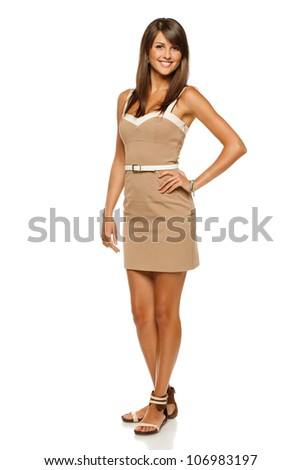 Full length portrait of trendy young woman in elegant beige dress smiling against white background - stock photo