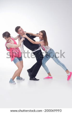 Full length portrait of two attractive teenage girls fighting for one fellow, isolated on white background. Concept of love, friendship, rivalry - stock photo