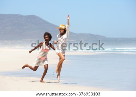 Full length portrait of two carefree young women walking barefoot on beach - stock photo