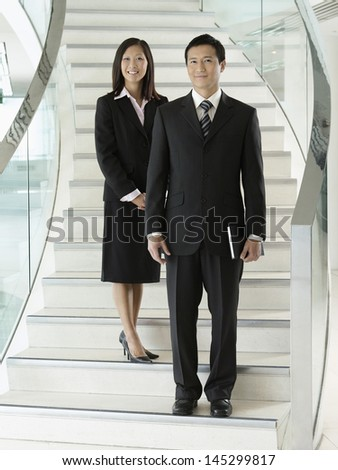 Full length portrait of two confident businesspeople standing on stairs - stock photo