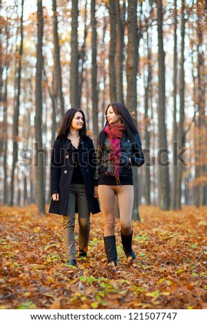 Full length portrait of two happy girlfriends walking in the woods while holding hands - stock photo