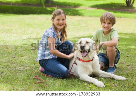 Full length portrait of two kids playing with pet dog at the park - stock photo