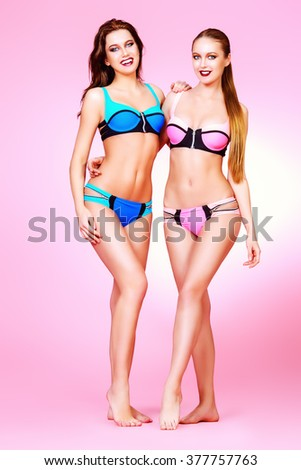 Full length portrait of two pretty girls in summer swimsuits posing together over pink background. Summer fashion. - stock photo