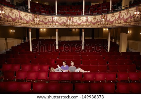 Full length portrait of two young women sitting in theatre stall with scripts - stock photo