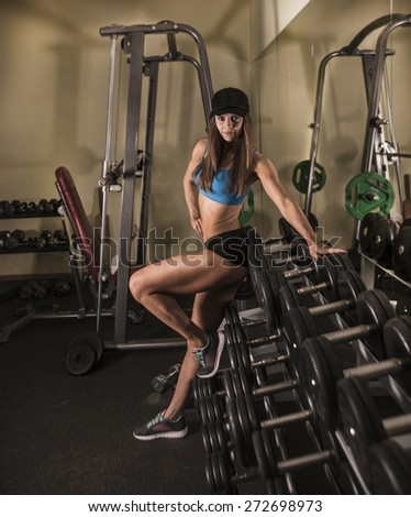 full length portrait of Young adult fit sporty girl poising near shelf with metal dumbbell in gym room space Cute slim woman wear cap and sports cloth look at camera along wall with mirror reflection  - stock photo