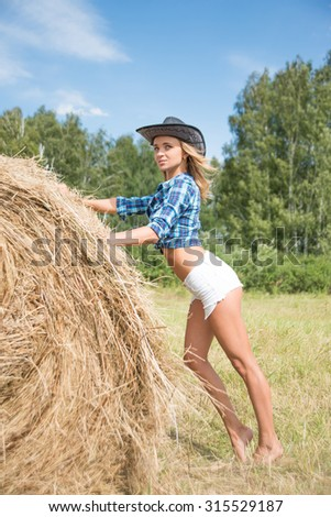 full length Portrait of young adult sexy woman standing next to a stack of hay in sunlight against blue sky with clouds and summer forest Empty copy space for inscription Cowgirl wear black hat  - stock photo