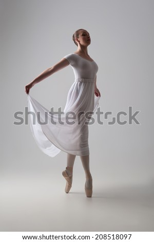 Full length portrait of young and beautiful modern style ballet dancer posing isolated on grey background, studio shot - stock photo