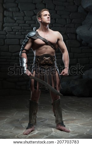 Full length portrait of young attractive warrior gladiator with muscular body posing with sword on dark background. Concept of masculine power, strength - stock photo