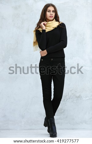 Full length portrait of young beautiful brunette woman with wavy long hair stares into camera posing against painted wall - stock photo