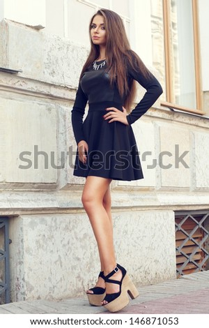 full length portrait of young beautiful sexy stylish girl wearing black dress and black shoes posing at city street against house wall - stock photo