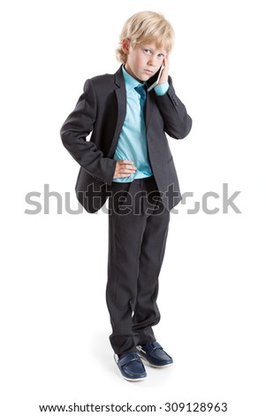 Full length portrait of young boy a businessman standing on white background with mobile phone in hand - stock photo