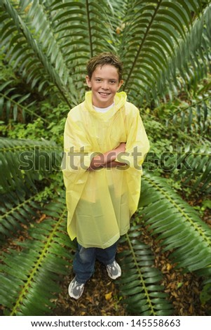Full length portrait of young boy standing by large fern in forest - stock photo