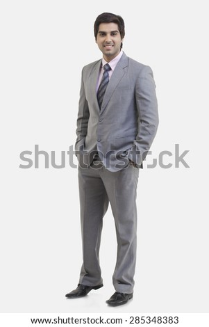 Full length portrait of young businessman with hands in pockets standing against white background - stock photo