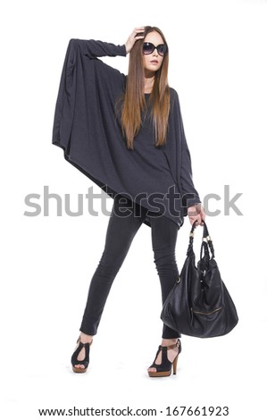 full-length portrait of young Casual woman in sunglasses with bag posing   - stock photo