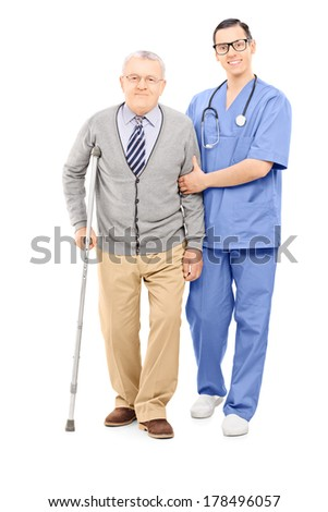 Full length portrait of young doctor helping an elderly gentleman with crutch isolated on white background - stock photo