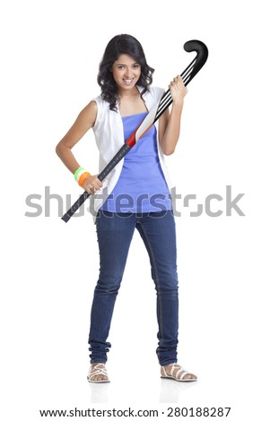 Full length portrait of young female in casual wear holding hockey stick over white background - stock photo