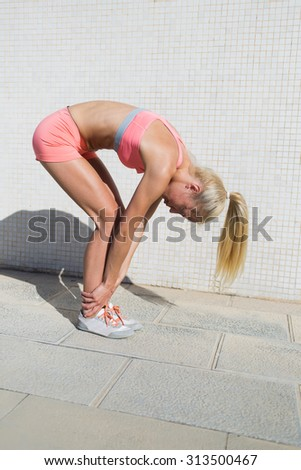 Full length portrait of young female runner with slender body stretching muscles of the body before a morning run, fit woman dressed in sportswear doing warm up exercise outdoors in sunny summer day  - stock photo