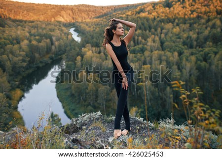 Full-length portrait of young girl doing yoga in the mountains - stock photo