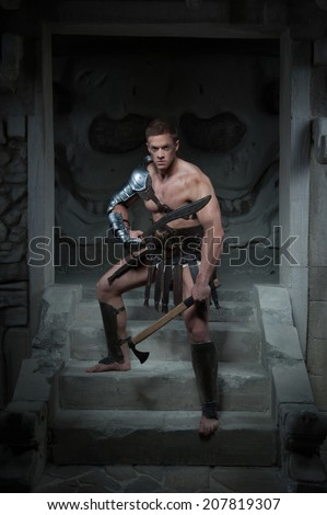 Full length portrait of young handsome muscular man Gladiator in armour standing on steps of ancient temple with sword and axe, concept of power, aggression, masculinity - stock photo