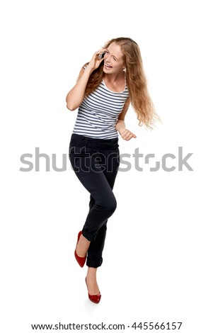 Full length portrait of young, happy laughing beautiful woman talking on cell phone showing yes gesture celebrating success, over white background - stock photo