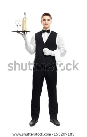 full length portrait of young happy smiling waiter with bottle of white wine and stemware glass on tray isolated on white background - stock photo