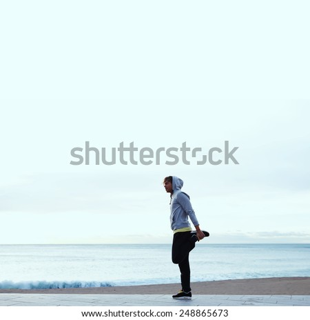 Full length portrait of young jogger stretching in the morning on seaside, young athletic man doing stretches next to the beach - stock photo